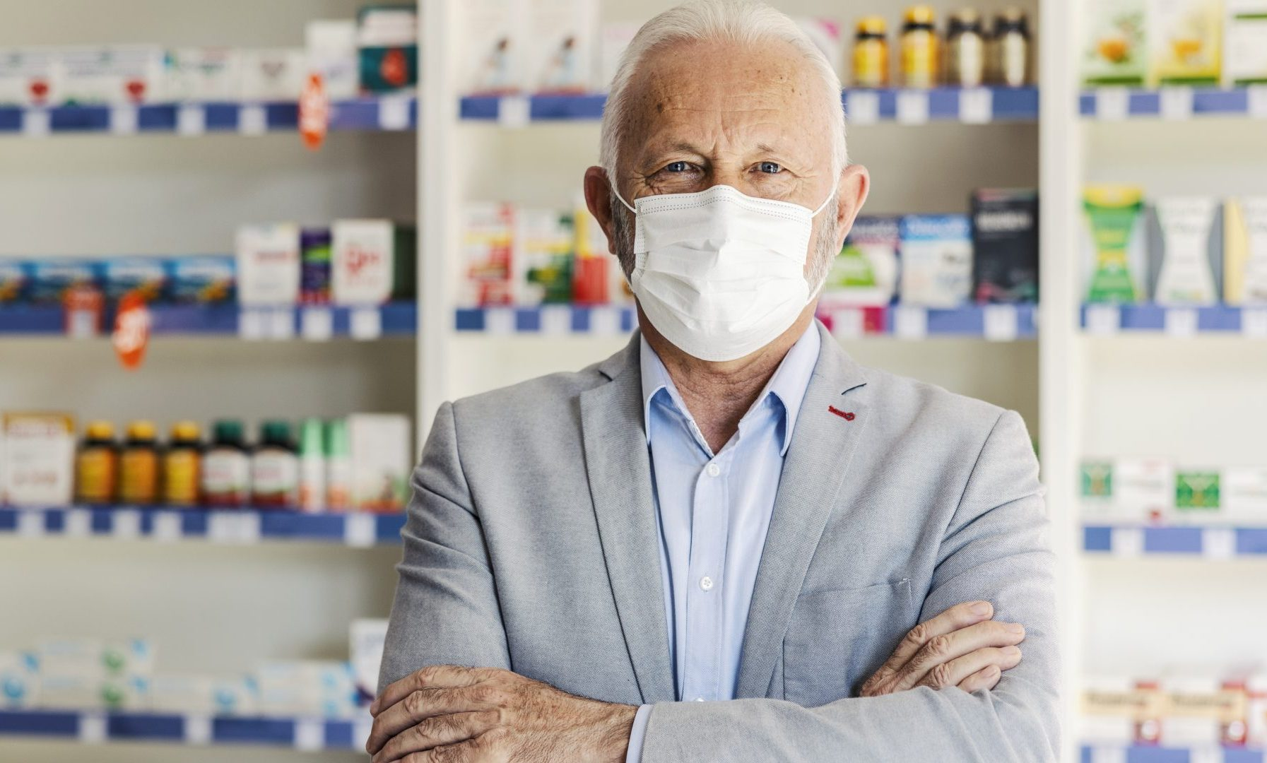 Senior pharmacist with his arms crossed is standing in a pharmacy, wearing a face mask.