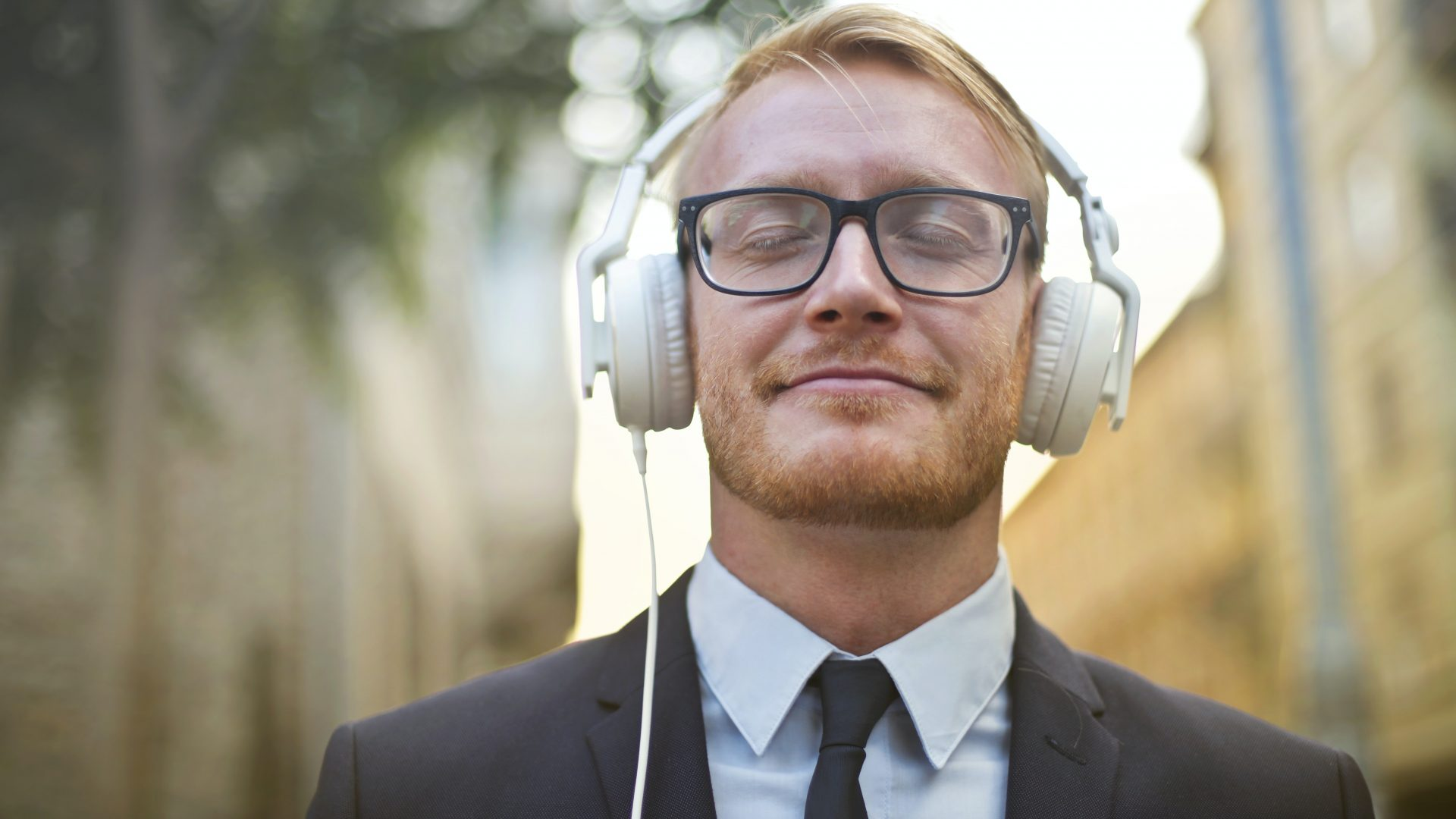 White man in suit and glasses listens to headphones outside